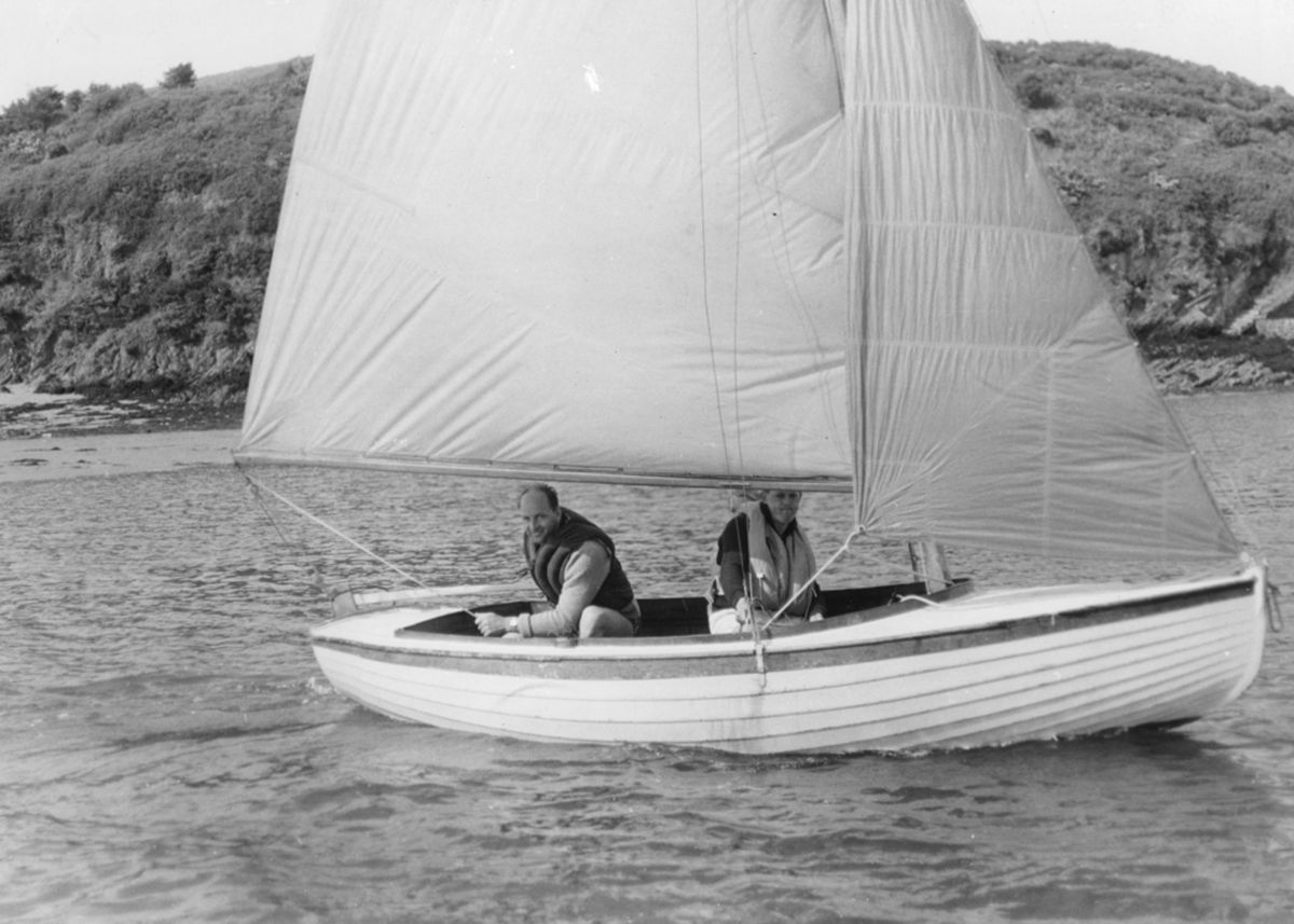 Two men sailing a wooden dinghy near Mousehole